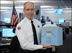 Lt. Matthew Hertzfeld holds the Smile Basket, which is  sent around the country from fire dispatchers who have dealt with line-of-duty deaths. The basket is filled with goodies and messages of support.