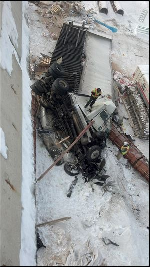 Emergency crews examine the wreckage after a collision between a car and a tractor-trailer sent the rig careening off the bridge from northbound I-475 onto Manley Road in Maumee.