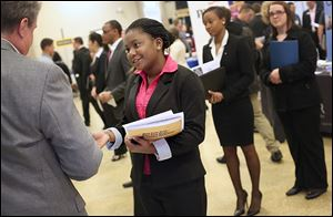 Finance major Ezinwa Omodom, center, discusses internships with a representative of  3M Frontline during a job fair at the University of Toledo's College of Business and Innovation. A U.S. report Friday  showed the sizable employment gap between those with college degrees and those without a high school diploma.