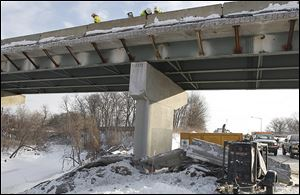 Contractors fix the barrier wall on the I-475 bridge, which was damaged by a tractor-trailer that toppled off the bridge. The damaged barrier wall is seen on the ground.