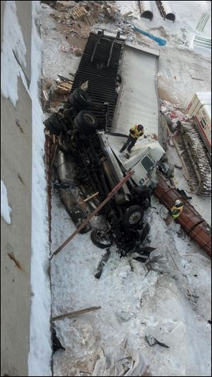 Crews examine the damaged truck early today that fell off the I-475 overpass Thursday night.
