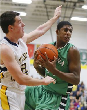 Ottawa Hills' Ellis Cummings grabs one of his seven rebounds on Friday night. Toledo Christian's Nathan Walton is at left.