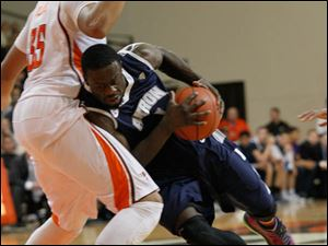 Akron's Demetrius Treadwell drives into BGSU's Cameron Black in the first half.