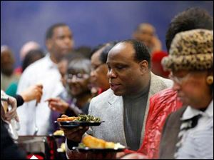 Steam rises as Pastor K. David Johnson of Third Baptist Church of Toledo goes through the buffet line.