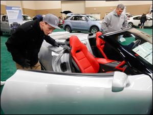 Cam Smith III of Toledo looks at the interior of a 2014 Corvette Convertible during the last day of the Toledo Auto Show.