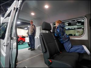 Sean Marko, left, stands upright in the back of a 2014 Mercedes-Benz Sprinter cargo van while his son, Darin, peaks over the seat.