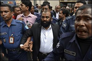One of the two owners of Tazreen Fashions Ltd., Delwar Hossain, center, is escorted by security personnel Sunday to a court in Dhaka, Bangladesh.