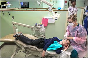 Isaac Truman, 9, waits for dental hygiene student Jen Donaldson to resume cleaning his teeth at Owens' clinic. Student volunteers outnumbered those already in practice.