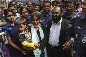 Two owners of Tazreen Fashions Ltd., Delwar Hossain, center left, and his wife, Mahmuda Akter, right, are escorted by security personnel on Sunday to a court in Dhaka, Bangladesh. The owners of a Bangladesh garment factory where 112 workers died in a fire two years ago surrendered on Sunday and sought bail after they were charged with homicide.