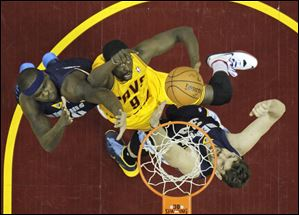 The Cavaliers' Luol Deng, center, shoots between Memphis Grizzlies defenders Zach Randolph, left, and Marc Gasol on Sunday night in Cleveland.