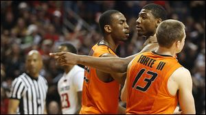 Oklahoma State's Markel Brown, left, and Phil Forte, right, hold Marcus Smart after Smart shoved a fan during their game Saturday night in Lubbock, Texas.