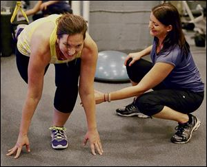 Working mom Regina Camplin works out with health coach Nicole Copare at TV Fitness Pros in Orlando, Fla.