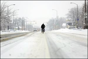 A bicycle rider braves a fresh blanket of snow during a Sunday drive down the middle of Summit Street.