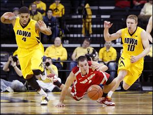 Ohio State's Aaron Craft dives for the ball between Iowa's Roy Devyn Marble, left, and Mike Gesell. The Buckeyes have won three games in a row after losing five of six. O