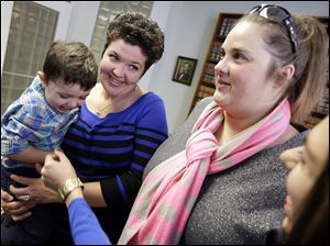 Nicole Yorksmith, left, holds her son,  while standing with her partner Pam Yorksmith. They are among four legally married gay couples who seek to force Ohio to recognize same-sex marriages on birth certificates.