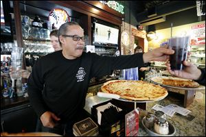 Retired Toledo Firefighter Steve Jones works the bar during a one-day fund-raiser Monday to benefit the Toledo Fire and Rescue Foundation at PizzaPapalis in Toledo.