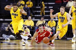 Ohio State's Aaron Craft dives for the ball between Iowa's Roy Devyn Marble, left, and Mike Gesell. The Buckeyes have won three games in a row after losing five of six. OSU hosts Michigan today.
