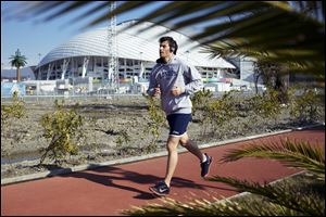 A man runs at a boardwalk near the Fisht Olympic Stadium in Olympic Park today in Sochi, Russia.