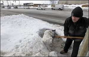 Sam Elseyed, employee of All Pro Quick Lube, shovels the snow and ice on the business' Secor Road front after a city inspector stopped by on Tuesday.
