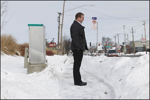 Dennis Kennedy, the city's  senior management of code enforcement, stands on a shoveled walk in front of Elder-Beerman on Secor.  The city has 'a spotty history of enforcement' of the ordinance that requires clearing walks of snow after a storm.