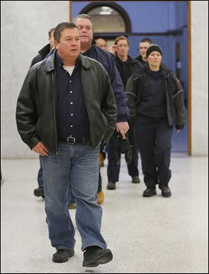 Toledo Fire Department personnel including Jeff Romstadt, president of Toledo Firefighters Local 92, front, walk to the courtroom Tuesday before the arraignment of Ray Abou-Arab.