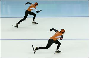 Margot Boer of the Netherlands, top, and Laurine van Riessen of the Netherlands compete in the second heat of the women's 500-meter speedskating race.