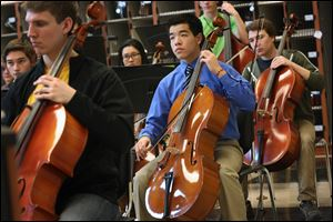 Starr Jiang, 15, center, plays the cello during orchestra practice at Northview High School.