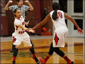 Rogers' Keyanna Austin low fives Akienreh Johnson during 2nd half.
