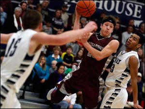 Rossford's Eric Davis passes in front of Lake's Brandyn Neal.