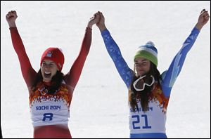 Women's downhill gold medalists Switzerland's Dominique Gisin, left, and Slovenia's Tina Maze, right, hold hands during a flower ceremony today.