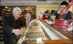 Bruce Brodbeck of Toledo selects chocolate pieces for his wife at Maumee Valley Chocolate and Candy shop in Maumee on Wednesday as shop co-owner Jason Sieminski helps him.