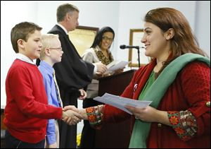 Bahija Gouriny, formerly of Morocco, shakes hands with Waterville Primary School third grader Aidan Funk after receiving her certificate of citizenship during a naturalization ceremony at the Browning Care Center in Waterville.