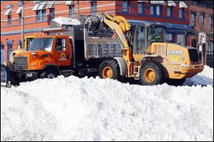 City workers clear snow at South St. Clair and Lafayette streets in downtown Toledo during record-cold temperatures Wednesday.