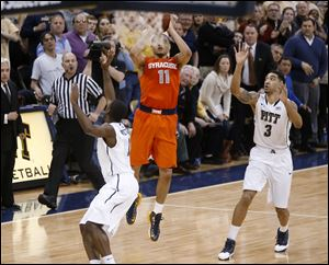 Syracuse's Tyler Ennis shoots a 3-pointer between Pittsburgh's Cameron Wright (3) and Josh Newkirk, left, in the final second Wednesday in Pittsburgh. The shot went in and Syracuse won 58-56.