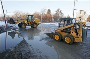 Water and ice are cleared from the Anthony Wayne Trail near Glendale after a water-main break.