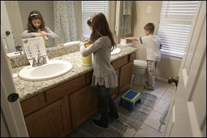 Lily Cherry, 8, cleans her bathroom as her brother Aiden, 6, right, puts out a new roll of toilet paper at their home in Kingwood, Texas. Their mother, Andrea Cherry, has passed on her childhood practice of doing chores to her children, believing it gives them a sense of family responsibility.