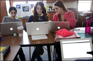 Leen Yassine, 13, left, Parker Caesar, 13, center, and Libby Stupica, 14, discuss stock prices while selecting companies to add to their portfolio at Toledo's West Side Montessori school.