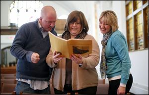 From left: Mike McArthur, Heather Meyer, and Lori Reid look at a 1970-1971 yearbook of the congregation.