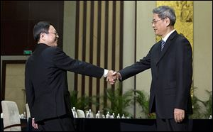 Wang Yu-chi,  left, head of Taiwan's Mainland Affairs Council, greets Zhang Zhijun, director of China's Taiwan Affairs Office, before their meeting in China last week.