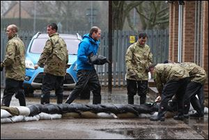 Britain's Prince William, The Duke of Cambridge, center, unloads sandbags, with members of the armed forces on Friday in Datchet, England.