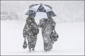 Shoppers make their way through heavy snow after shopping at the Big  Y supermarket on Memorial Drive  in Chicopee, Mass.,  Thursday.