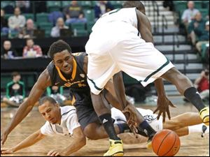 Toledo's Justin Drummond (4) is caught up between Eastern Michigan's J.R. Sims, left, and Glenn Bryant, right, in a scramble for a loose ball.