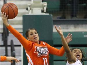 Bowling Green's Jillian Halfhill (11) pulls down a rebound over Eastern Michigan's Cha Sweeney (24).