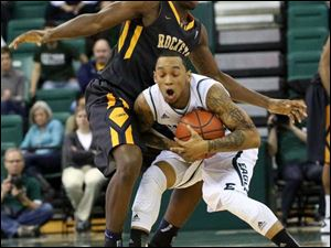 Toledo's Justin Drummond (4) fouls Eastern Michigan's Mike Talley (1) during the second half.