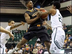 Toledo's Jonathan Williams (1) is stopped on his drive down the lane by Eastern Michigan's Darell Combs (25).