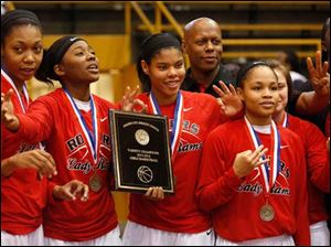 From left: Tori Easley, Sasha Dailey, Jasmyne Smith, head coach Lamar Smith, and Keyanna Austin celebrate their victory during the girl's City League championship basketball game against Start at Waite High School in Toledo.