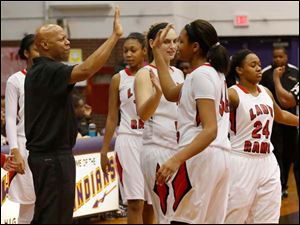 Rogers' head coach Lamar Smith high-fives Keasja Peace.