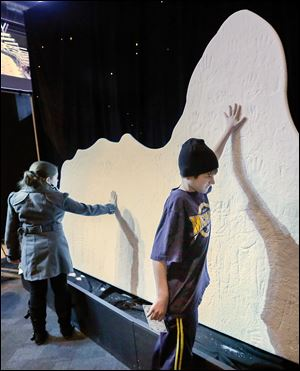 Bronson Ulery, 12, of Sylvania gets hands-on with a mini iceberg replica that was cool — both figuratively and literally — as he toured 'Titanic: The Artifact Exhibition' at the Imagination Station.