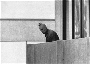 Amasked terrorist stands on the balcony of the building where the Arab group Black September was holding members of the Israeli Olympic team hostage during the 1972 Summer Olympics in Munich, Germany.