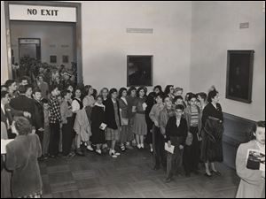 Toledo residents and Catawba Island school students wait in line inside the Toledo Museum of Art.